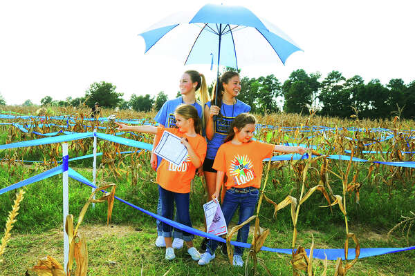 Rylee Roger, left, and Stella Oncken both point to the way out of the corn maze at Tomball's Salem Lutheran Church. The girls are helping maze guides, back left, Lindsey Bills and Jardan Husfed, right, find the way out of the maze.
