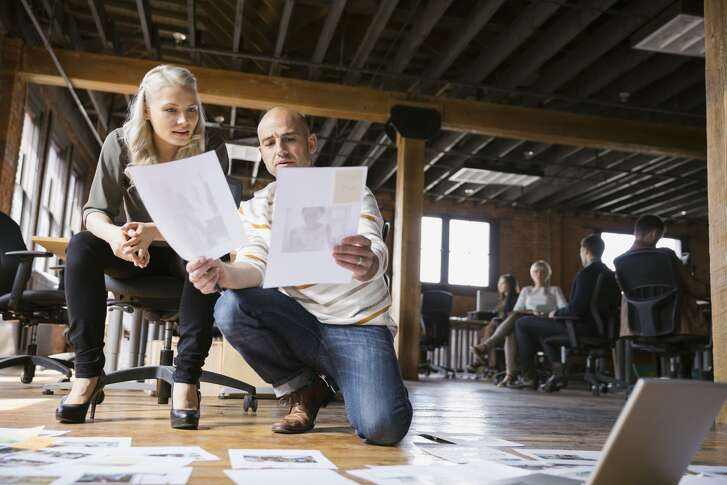 Business people review documents in an office. (Hero Images / Getty Images)