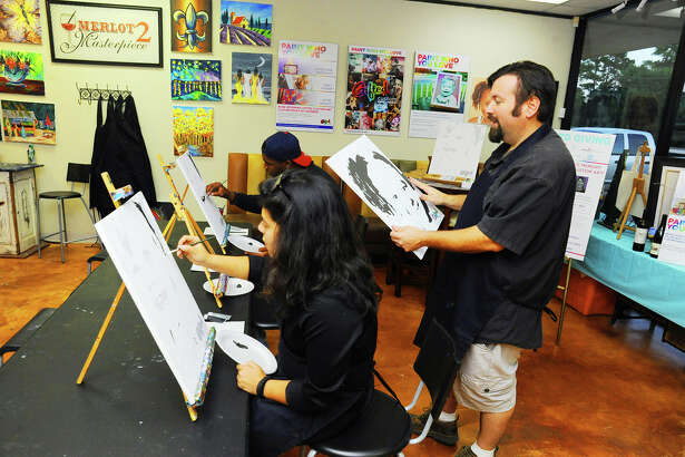 (L) Alejandna Jimenes and (far center) Dadius Wilson try there hand at painting the pre-drawed canvas, while owner Jeff Bernal observe the clients skill and style.