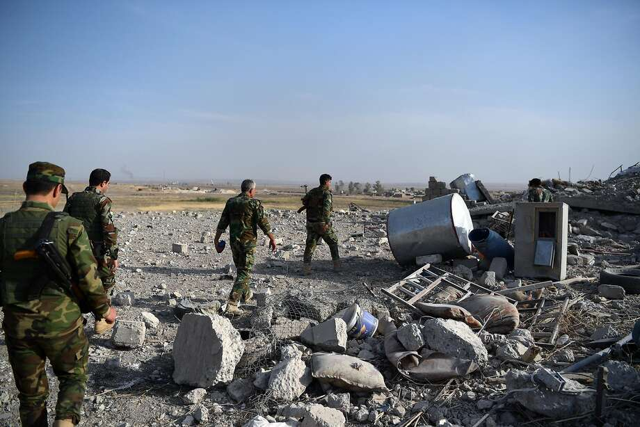 Kurdish soldiers walk through the rubble of a village previously held by the Islamic State near Mosul. Photo: Carl Court, Getty Images