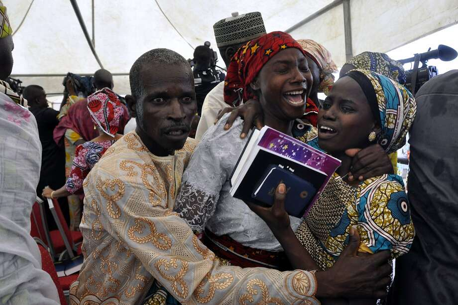 One of the kidnapped girls celebrates with family members during an church survives held in Abuja, Nigeria, Sunday, Oct. 16, 2016. The girls were released Thursday and flown to Abuja, Nigeria's capital, but it's taken days for the parents to arrive.  The families came from the remote northeastern town of Chibok, where nearly 300 girls were kidnapped on April 2014 in a mass abduction that shocked the world. Dozens of schoolgirls escaped in the first few hours but after last week's release, 197 remain captive. (AP Photo/Olamikan Gbemiga) Photo: Olamikan Gbemiga, Associated Press