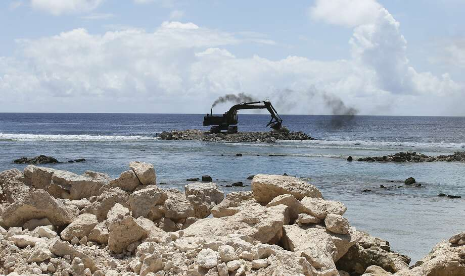 A heavy earth mover building a sea wall on Majuro Atoll, Marshall. Rising seas in the Marshall Islands can be seen on many of the Atolls in the group as more coastline disappears and vegetation is washed away. The US military ignored warnings about rising seas to build a space radar costing nearly a billion dollars on a tiny atoll in the Marshall Islands. The Space Fence system is considered vital for keeping astronauts and satellites safe by tracking space junk as small as a baseball.(AP Photo/Rob Griffith) Photo: Rob Griffith, Associated Press
