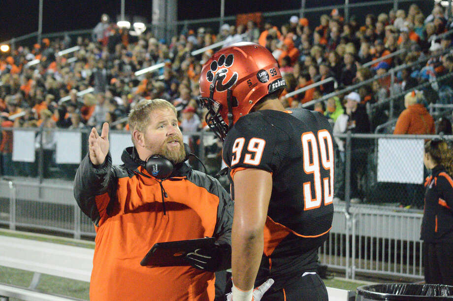 Edwardsville defensive coordinator Kelsey Pickering, left, talks to junior defensive end A.J. Epenesa during last Friday's Homecoming game against Alton.
