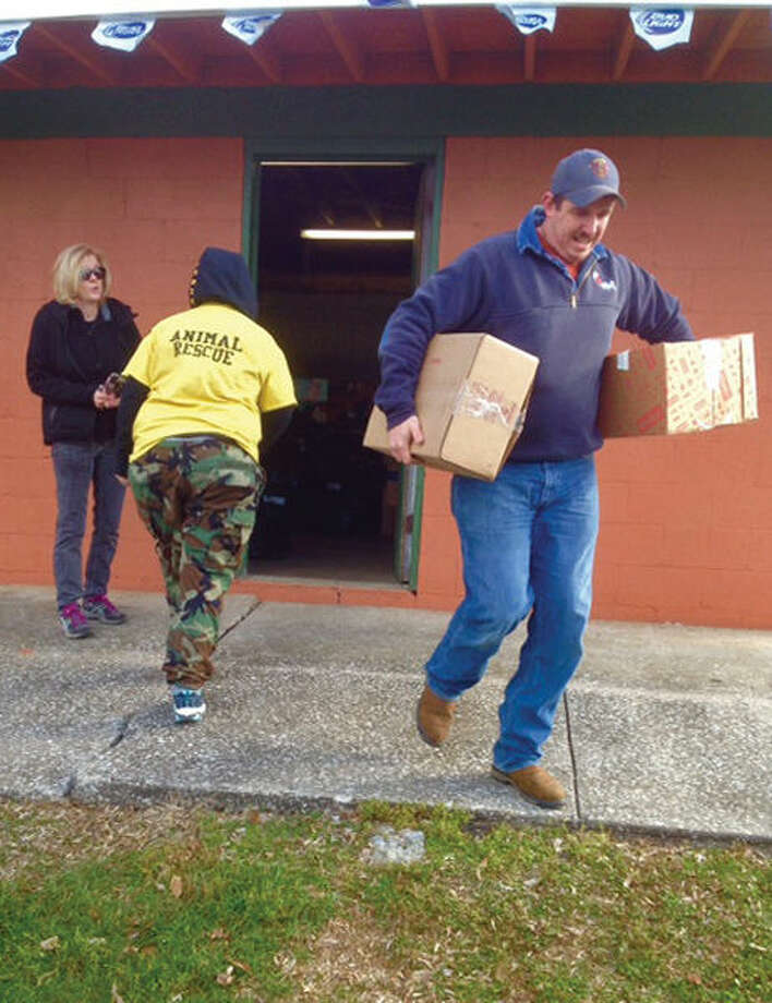 A volunteer carries supplies donated for recent area flood victims out of American Legion Post 199 on Monday morning. Photo: Steve Horrell/Intelligencer
