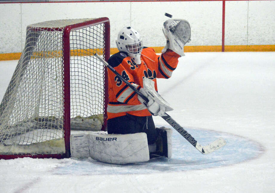 Edwardsville senior goalie Blake Johnson tries to make a save on a shot late in the second period during Monday's game at the East Alton Ice Arena.