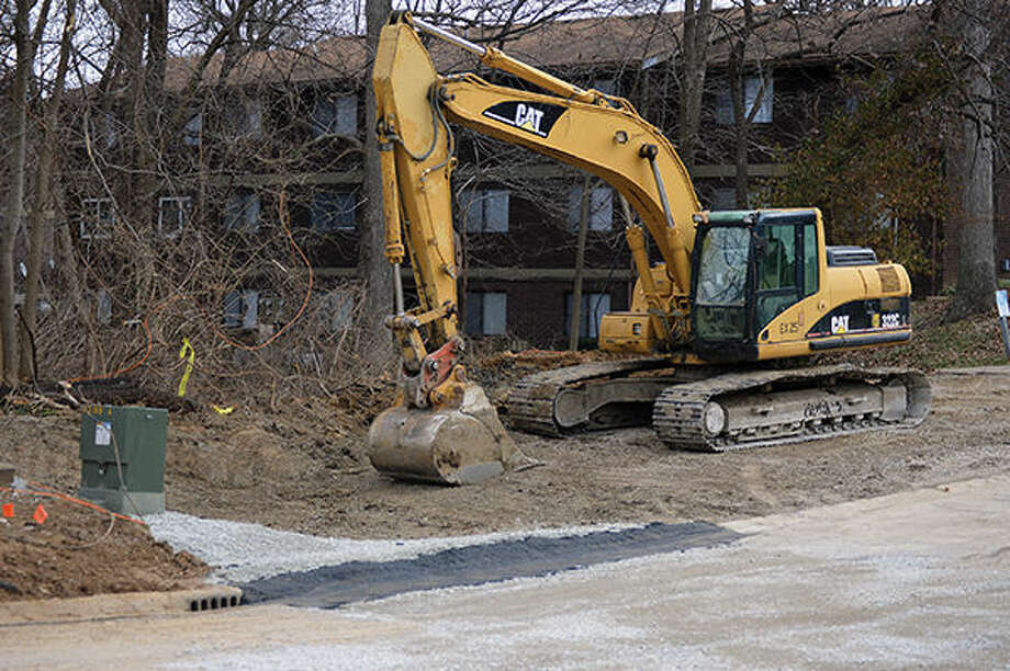 An excavator on Thursday sits on top of the dirt that has been used to fill in a sinkhole that developed on Devon Court in Edwardsville following the rains of Dec. 26 to 28. Photo: Matthew Kamp/Intelligencer