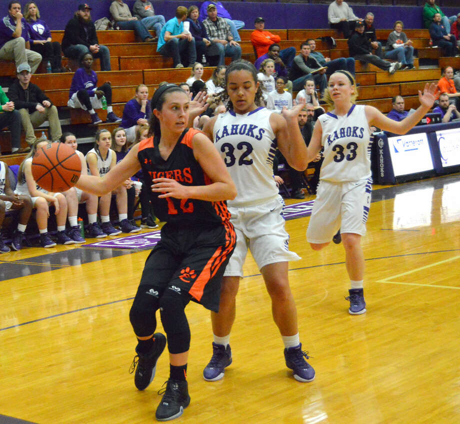 Edwardsville guard Makenzie Silvey looks to elude Collinsville's Gabby Morgan, center, with Carlee Mahan also in on the play.