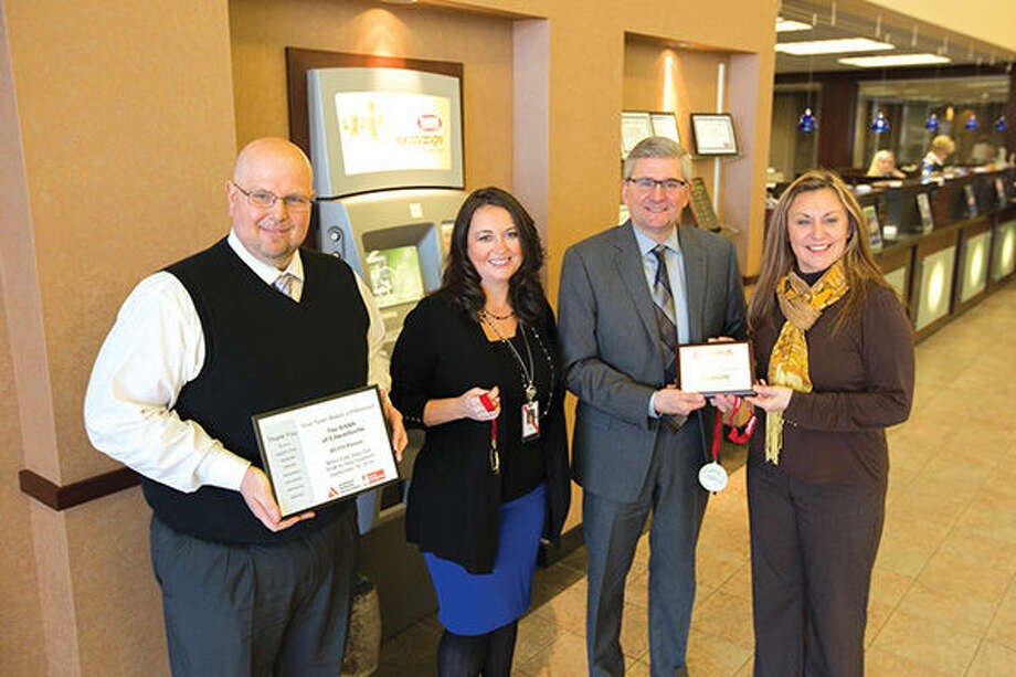 American Diabetes Association-Metro East Manager Rawnie Berry, right, presented TheBANK of Edwardsville with plaques and medals Monday, Jan. 4, at the Main Office in Edwardsville for its support of the 2015 Metro East Step Out: Walk to Stop Diabetes. Representing TheBANK, from left, are: Bill Yarbrough, community relations/communication coordinator; Danielle Smith, vice president of human resources; and Kevin Powers, president and CEO. Photo: For The Intelligencer