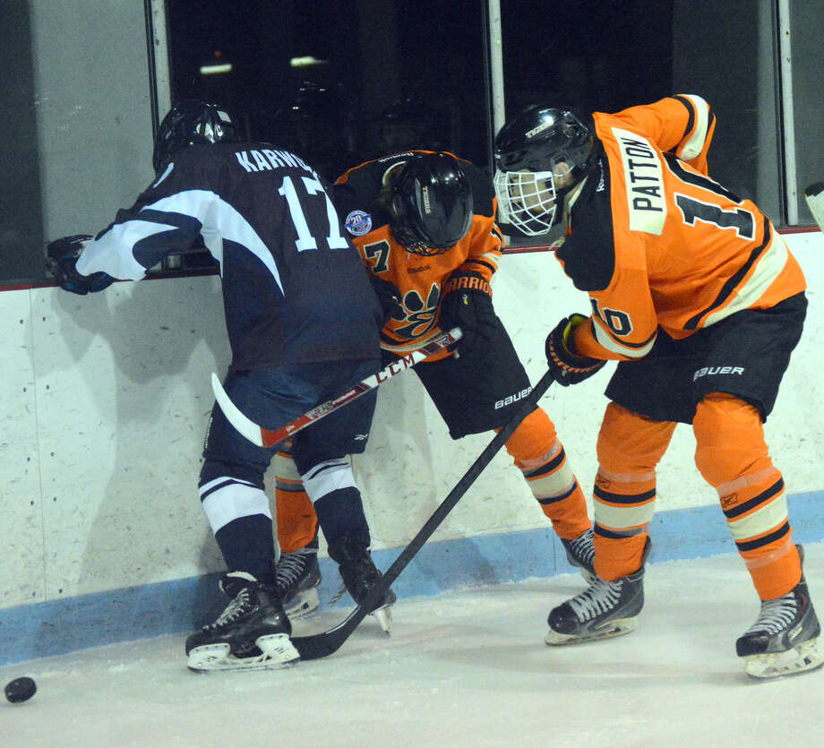 Edwardsville's Reilly Patton, left, and Collin Fischer, center, battle for a loose puck along the boards in the first period.