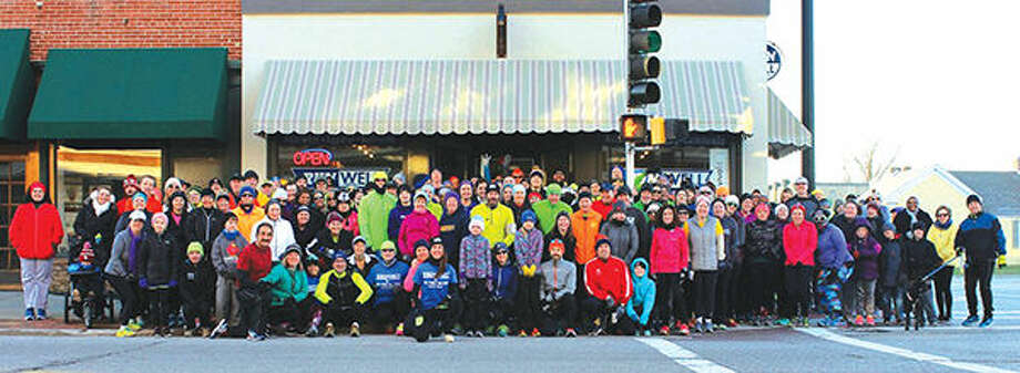 A crowd gathers outside of RunWell on Vandalia Street prior to a run on New Year's Day. RunWell is moving to a new location on North Main Street and will have a grand reopening on Feb. 26. Photo: For The Intelligencer