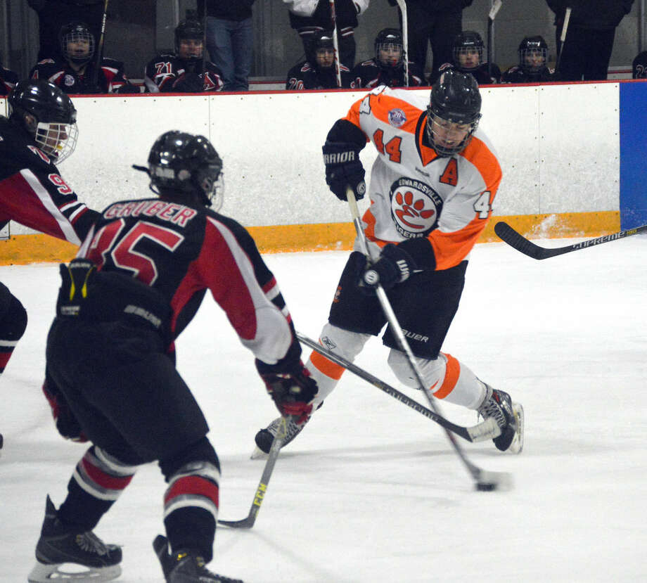 Edwardsville junior Tyler Schaeffer, right, attempts a wrist shot with two Triad defensemen trying to knock the puck away in the first period at the East Alton Ice Arena.