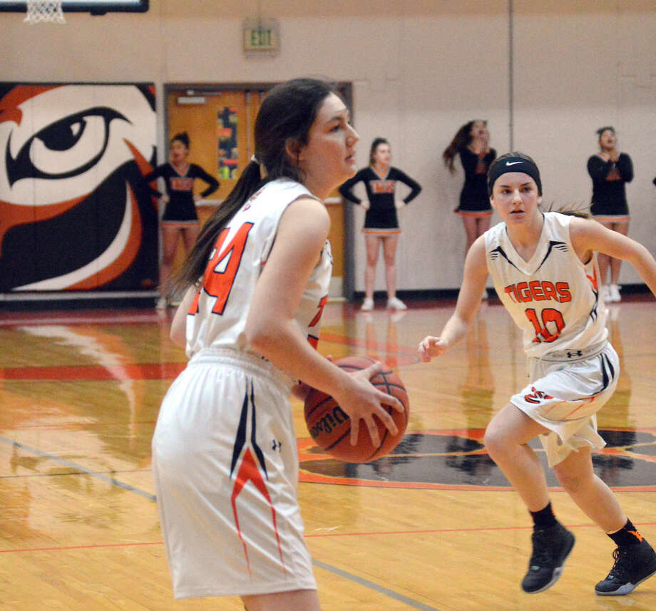 Edwardsville senior Kayla Johnson looks for an open teammate as Lorie Cashdollar tries to elude an Alton defender on Friday at Lucco-Jackson Gymnasium.