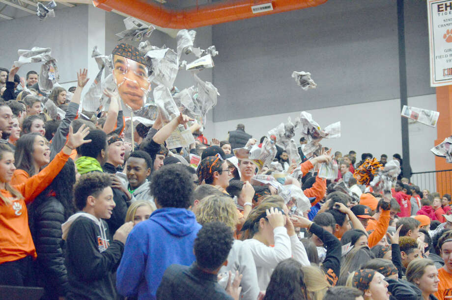 The Edwardsville student section throws newspapers up into the air after pretending to ignore the introduction of the Alton boys' basketball team Friday at the Lucco-Jackson Gymnasium.
