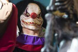 """Halloween costumes and props, including a """"scary"""" clown mask, are seen for sale at Total Party, a party store, in Arlington, Virginia, October 7, 2016. / AFP PHOTO / SAUL LOEBSAUL LOEB/AFP/Getty Images"""