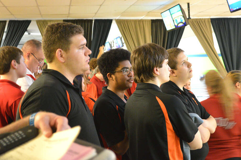 Members of the Edwardsville boys' bowling team look at scores Wednesday afternoon during the fifth round of the Alton Invitational at Airport Bowl in Bethalto.