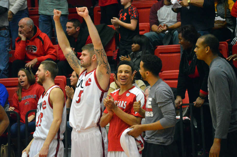 The SIUE men's basketball team celebrates from the bench after the Cougars clinched their first Ohio Valley Conference victory of the season Saturday at the Vadalabene Center.