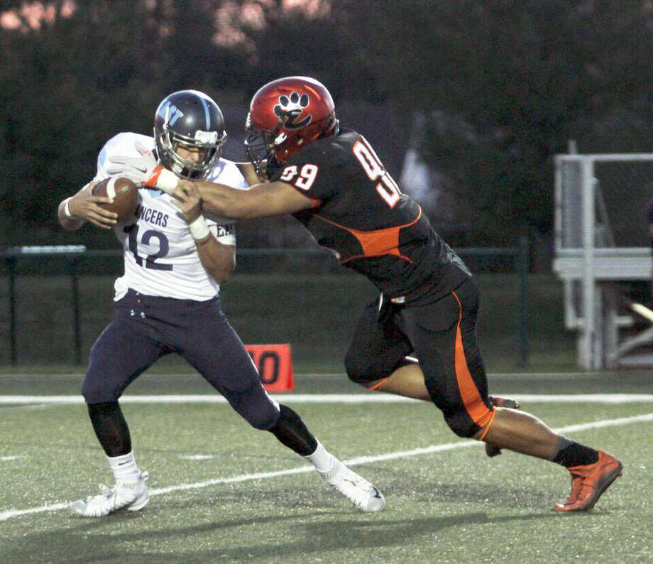 Edwardsville junior defensive end AJ Epenesa, right, grabs hold of Belleville East quarterback Drew Millas during a 2015 regular season game at the Edwardsville Sports Complex. Photo: Devin Kane/For The Intelligencer