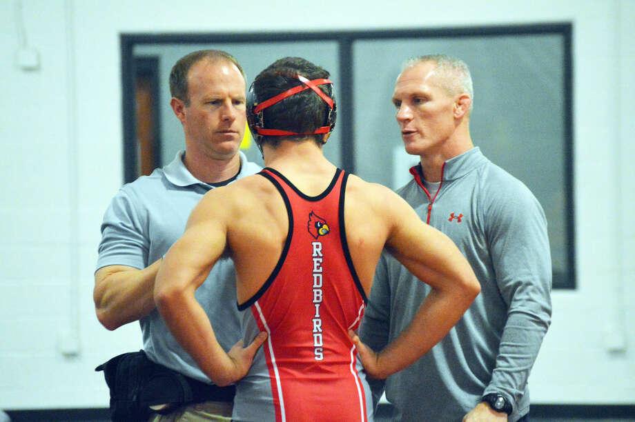 Edwardsville trainer Drew Dintelmann, left, checks on an Alton wrestler during a triangular match at EHS on Thursday.