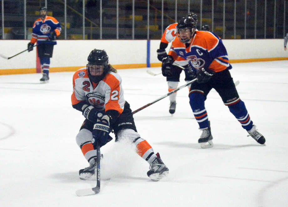 Edwardsville senior Tyler Hinterser, left, looks to fire a shot on goal midway through the second period Monday at the East Alton Ice Arena.