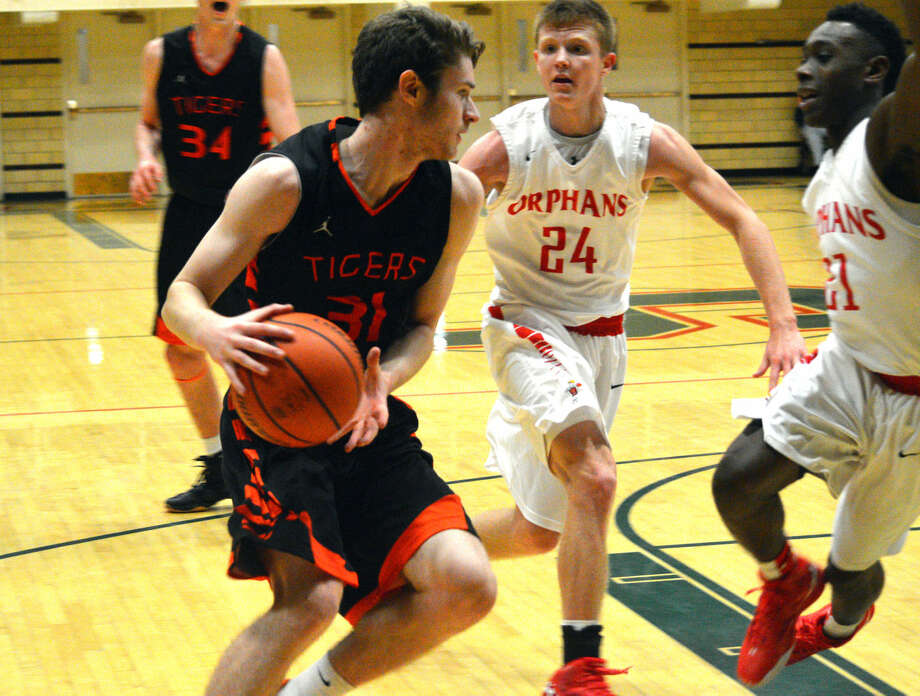 Edwardsville junior Oliver Stephen tries to get past two Centralia defenders during Saturday's championship game at the Salem Invitational.