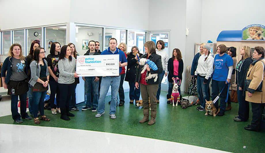 A Petco corporate executive, holding right side of check, presents a $90,000 donation to Partners 4 Pets, with director Lisa McCormick, holding dog in blue sweater, looking on. Photo: Zach Foote/Intelligencer