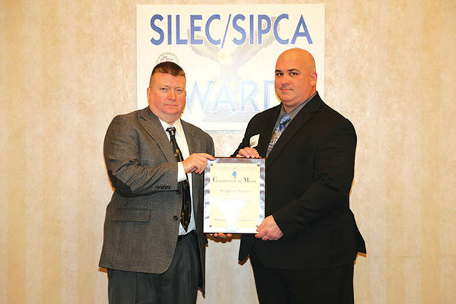 Maryville Police Detective Stephen Howe, right, displays his Southern Illinois Law Enforcement Commission/Southern Illinois Police Chief's Association award with Maryville Police Chief Rob Carpenter. Photo: For The Intelligencer