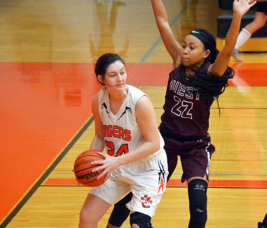 Edwardsville senior Kayla Johnson, left, looks for a teammate as Belleville West's Brittney Walker defends her in the post.