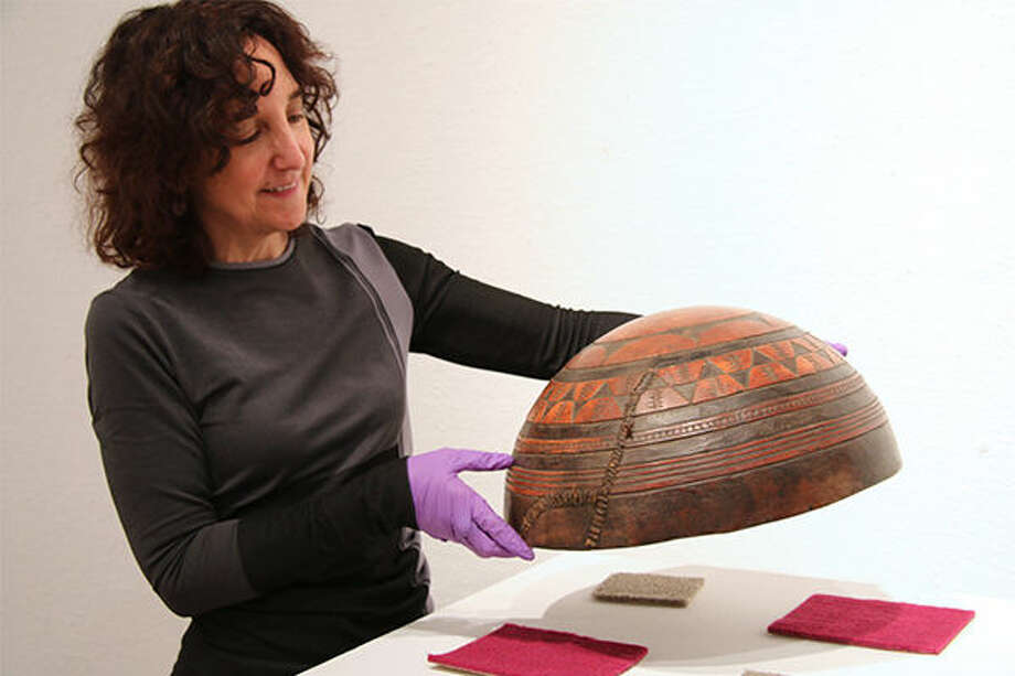 "Allyson Purpura, Krannert Art Museum's curator of African art and curator of the ""Spheres of Influence"" exhibition, holds an ocher-colored bowl made from a gourd. A section of the pot that has been repaired is visible. The bowl and other pieces from the museum's collection of African vessels are on display this spring. Photo: Julia Kelly"