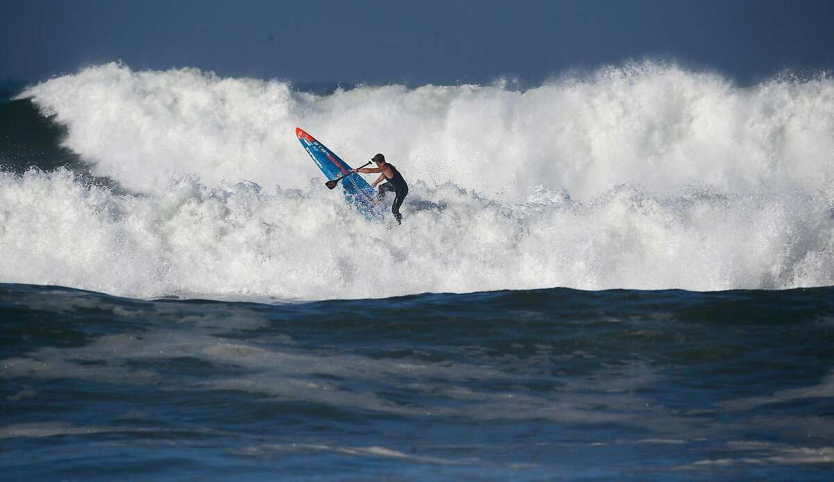 With the competition postponed until Wednesday Zane Schweitzer gets in a little practice in the surf off Ocean Beach on Tuesday October 18, 2016, to prepare for the Red Bull Heavy Water Stand Up Paddle Board competition in San Francisco, California.