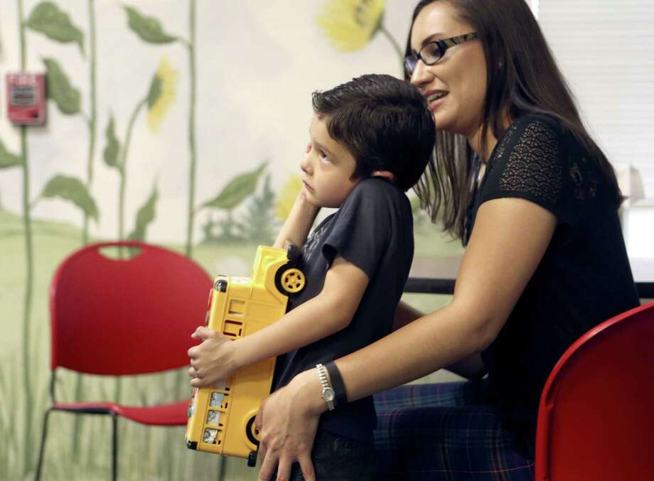 Joseph Sanchez observes a teacher as he stands with his mother, Linda Fierro, at Any Baby Can. He was 18 months old when his mother became concerned that he wasn't speaking. At age 3, he was diagnosed with autism spectrum disorder. A new coalition of groups that help people with autism has been formed in San Antonio. Photo: William Luther /San Antonio Express-News / © 2016 San Antonio Express-News