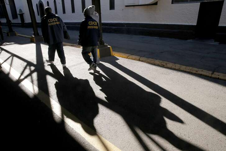 Prisoners walk through the grounds of the prison near death row at San Quentin State Prison on Tuesday December 29, 2015, in San Quentin, Calif.