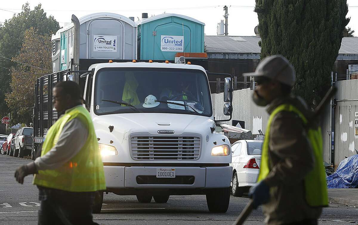 City workers do a sweep at the homeless encampment underInterstate 580in West Oakland.