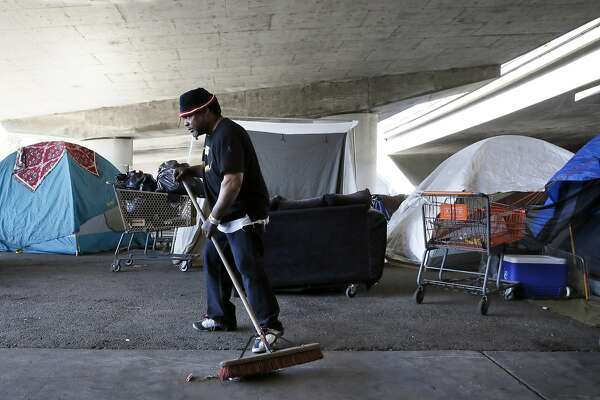 Campanella Martin sweeps the encampment where he is staying on Tuesday October 18, 2016, a day after the city of Oakland installed several amenities including portable toilets, a hand washing station and garbage and recycling cans at a homeless encampment under the I-580 freeway at 35th and Magnolia streets in Oakland, California.