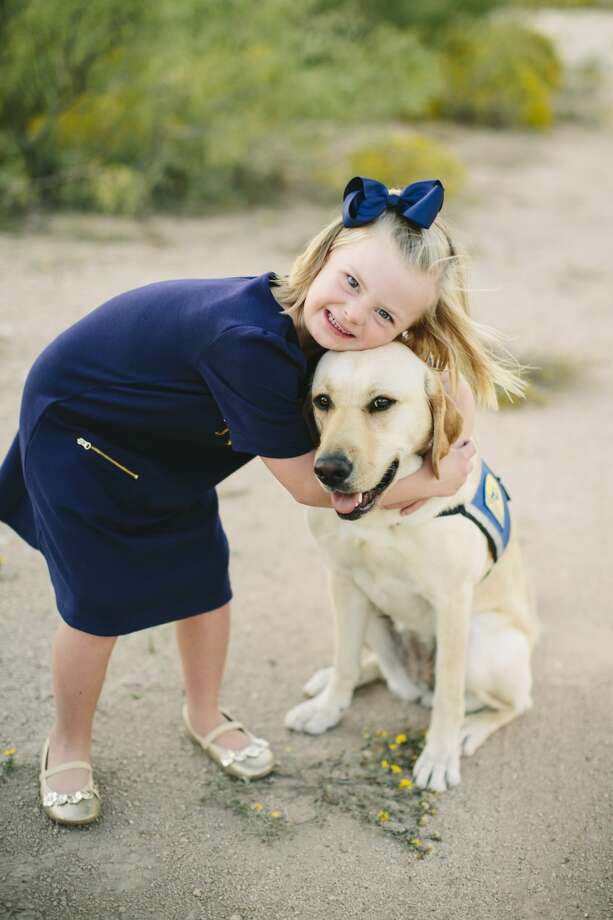 Emery Ham, 6, hugs and her canine companion, Piper.