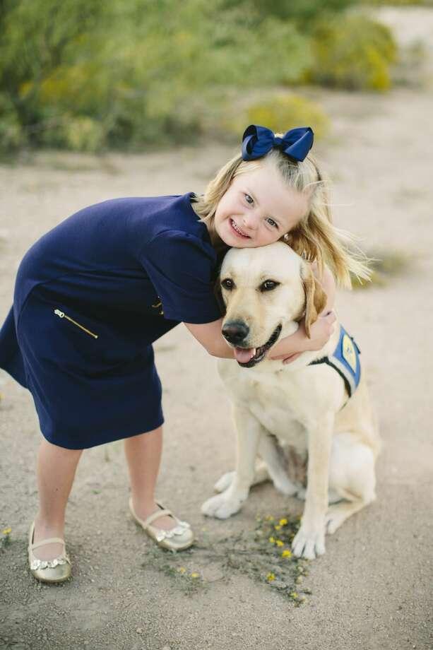 Emery Ham, 6, hugs and her canine companion, Piper. Photo: Courtesy Photo