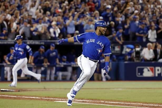 Toronto Blue Jays' Edwin Encarnacion celebrates after his two-RBI double against the Cleveland Indians during the seventh inning in Game 4 of baseball's American League Championship Series in Toronto, Tuesday Oct. 18, 2016. (Mark Blinch/The Canadian Press via AP)