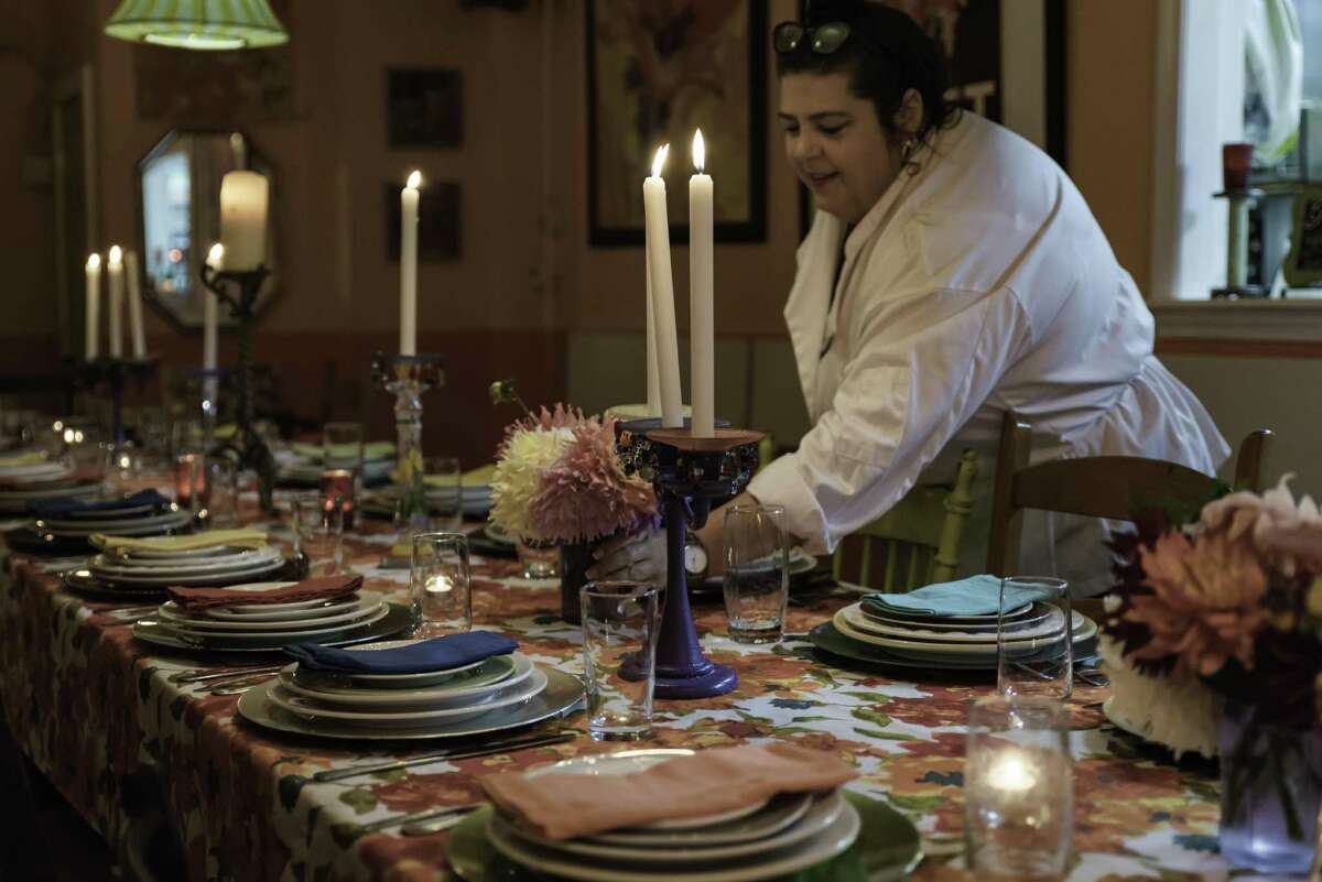 Carol Lentini, hostess and head chef, places a centerpiece on the communal dining table.