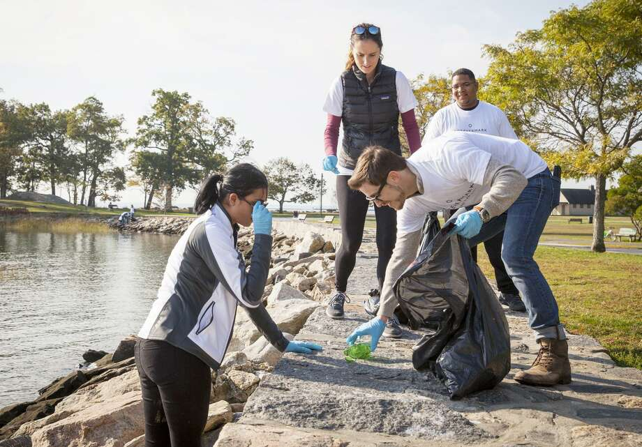 John Breznen, center, picks up a bottle at Cove Island Park. Photo: Contributed / Contributed Photo