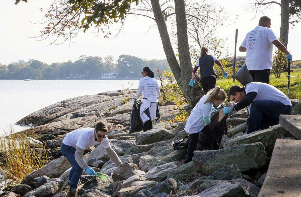 Volunteers from local jewelry stores pick up trash along the waterline at Cove Island Park in Stamford on Sunday.