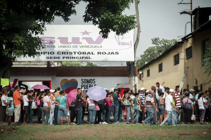 People stand in front of a Socialist Party office while waiting in line to buy groceries at a supermarket in Charallave, Venezuela, in April.