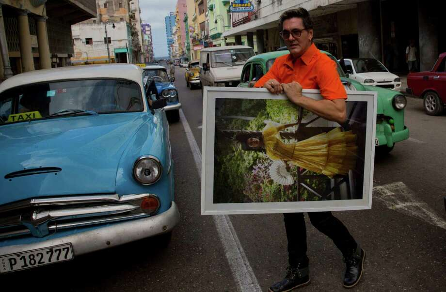 In this Oct. 14, 2016, photo, Cuban fashion designer Mario Freixas poses for a photo as he walks among vintage american cars on a street in Havana, Cuba. Freixas, a well-known designer who dresses many of the stars of state-run television, sells shirts for $20 and men's and women's pants for $30. (AP Photo/Ramon Espinosa) Photo: Ramon Espinosa, STF / Copyright 2016 The Associated Press. All rights reserved.