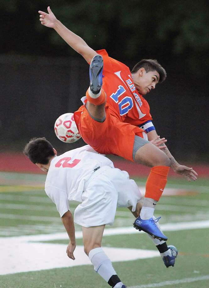 At left, Shoki Araki (#2) of Greenwich goes low for tha ball as Danbury's Edwin Rosano (#10) goes high flipping over the back of Araki during first half action of the boys high school soccer match between Greenwich High School and Danbury High School at Cardinal Stadium in Greenwich, Conn., Tuesday night, Oct. 18, 2016. Greenwich won the match 5 - 0. Photo: Bob Luckey Jr. / Hearst Connecticut Media / Greenwich Time