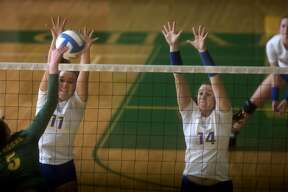 Midland High's Alexandria McMath, left, and Erin Sheridan block Dow's Isabel Velasquez's spike in the second set of Midland's match against Dow High Tuesday evening. Midland defeated Dow 25-10, 25-15, 25-14.
