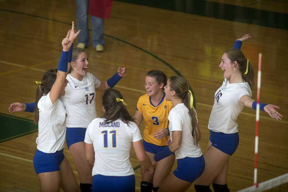 Members of the Midland High volleyball team celebrate winning the second set of their match against Dow High Tuesday evening. Midland defeated Dow 25-10, 25-15, 25-14 and won the Saginaw Valley League North with a record of 7-0. Photo: Brittney Lohmiller/Midland Daily News/Brittney Lohmiller