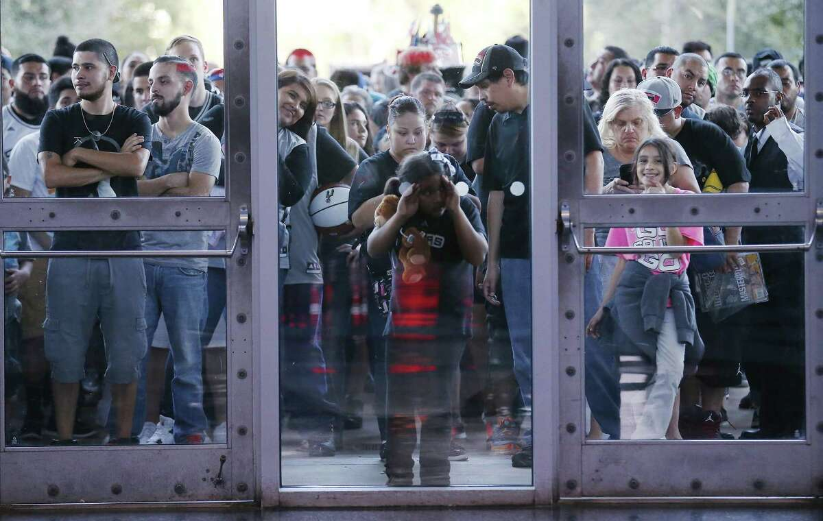 A young fans peers through a window awaiting to enter the AT&T Center for the Spurs' Silver and Black open scrimmage in 2016.