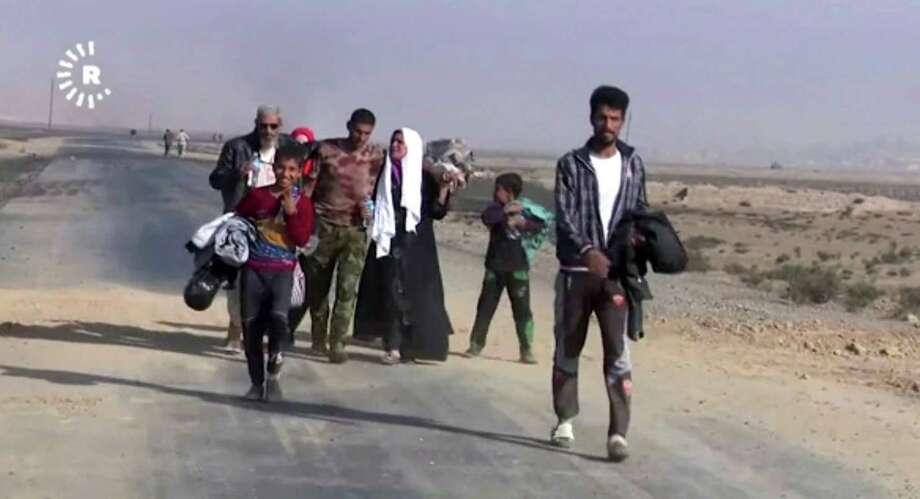 This image made from video by Rudaw News Agency shows a family fleeing Mosul, Iraq on Tuesday, Oct. 18, 2016. Residents who have endured more than two years of militant rule describe a city under siege, and say a new sense of terror has set in since Iraq announced the start of a long awaited operation to liberate its second largest city. (Rudaw News Agency via AP) ORG XMIT: XMA302 / Rudaw News Agency