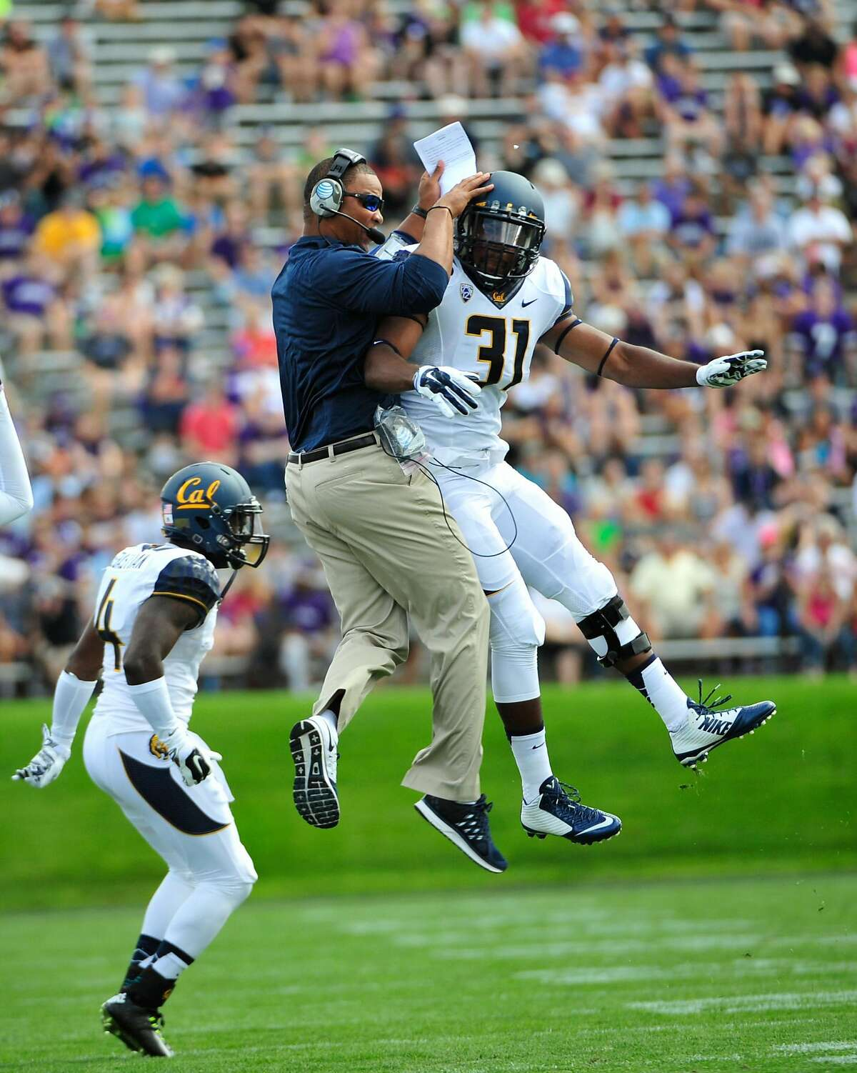 EVANSTON, IL- AUGUST 30: Raymond Davison #31 of the California Golden Bears celebrates a play with running backs coordinator Pierre Ingram during the first half in a game against the Northwestern Wildcats on August 30, 2014 at Ryan Field in Evanston, Illinois. (Photo by David Banks/Getty Images)