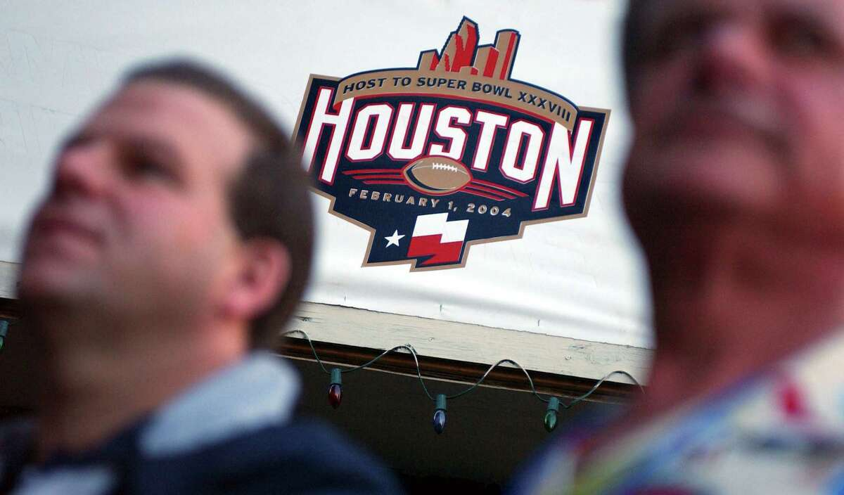 A Houston Super Bowl host logo is framed by Tilman Fertitta (left) and Jordy Tollett during a kickoff celebration for the upcoming Super Bowl XXXVIII on Main Street in downtown Houston, Saturday evening, April 12, 2003. (Smiley N. Pool/Chronicle)