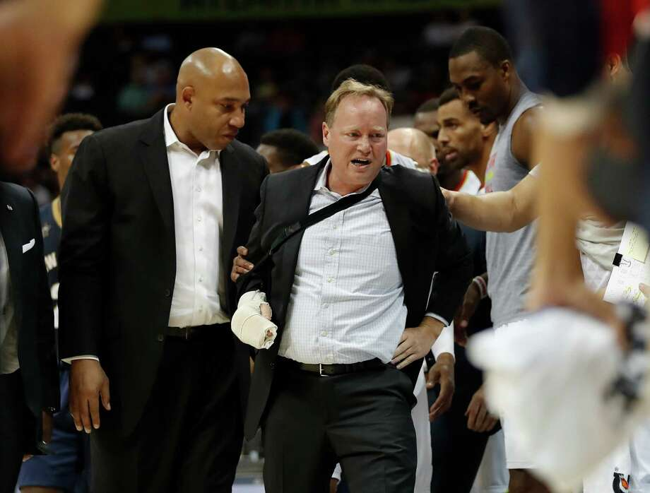 Atlanta Hawks coach Mike Budenholzer, center, is helped to his feet by assistant coach Darvin Ham, left, after he was run over along the sideline during the first half of the team's preseason NBA basketball game against the New Orleans Pelicans Tuesday, Oct. 18, 2016, in Atlanta. Budenholzer, who was already nursing an injured hand, left the game. (AP Photo/John Bazemore) Photo: John Bazemore, Associated Press / Copyright 2016 The Associated Press. All rights reserved.