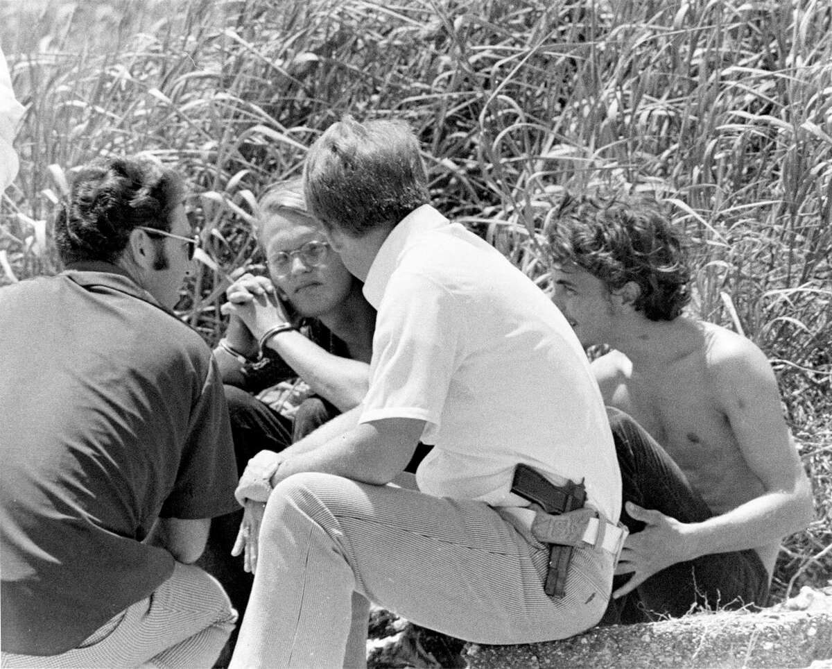 David Brooks and Elmer Wayne Henley chat with a police detective during search operations on High Island, August 1973. The beach was one of several locations being searched for bodies of the mass murder sex and torture ring.